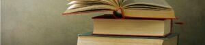 Stapel mit Büchern und einem aufgeschlagenen Buch als Motto-Bild für Buchbesprechungen der Berliner Paartherapeutin Julia Bellabarba